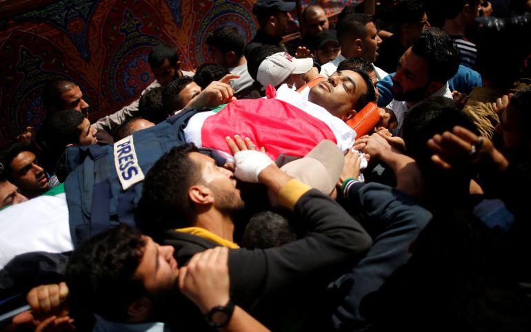 Compañeros del periodista palestino Yasser Murtaja, fallecido por un disparo del Ejército israelí, portando su cuerpo en Gaza