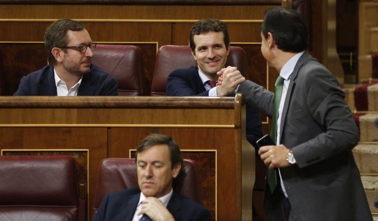 El diputado popular Fernando Martínez-Maíllo (d) saluda a su compañero de partido, Pablo Casado (2d), durante la sesión de control al Gobierno celebrada hoy en el Congreso.