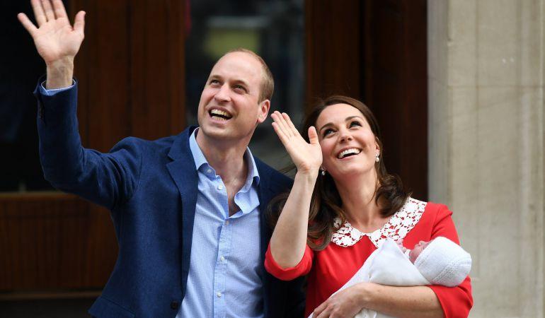 El príncipe Guillermo, duque de Cambridge (i), saluda al lado de su esposa, Catherine (d), duquesa de Cambridge, que sostiene a su hijo recién nacido este lunes.