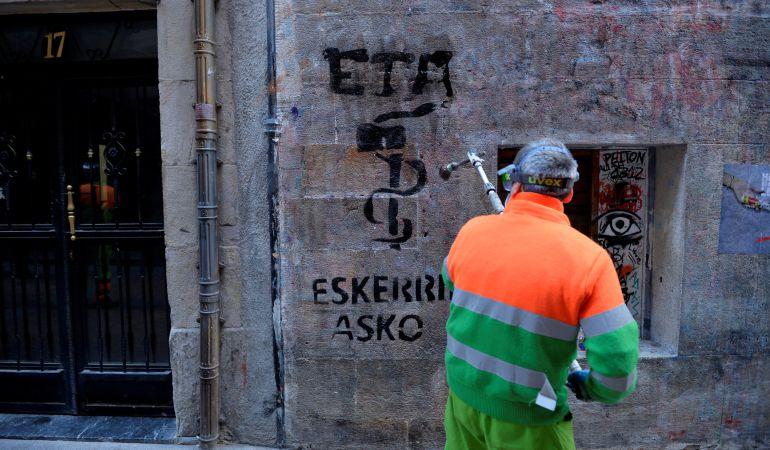 Un operario borra una pintada de agradecimiento a ETA en Bilbao.