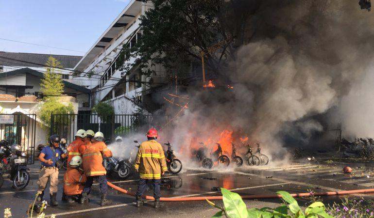 Los bomberos apagan un fuego en la puerta de una iglesia de Indonesia.