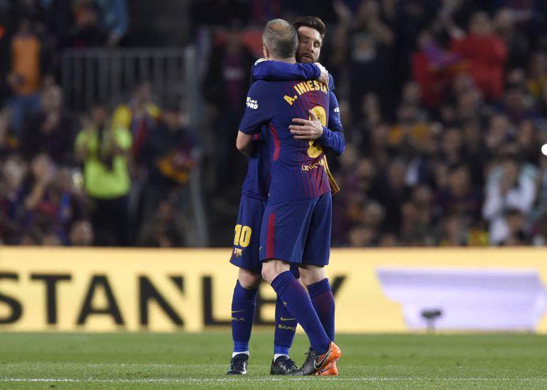 Andrés Iniesta y Leo Messi se abrazan durante el encuentro entre el FC Barcelona y el Real Madrid.