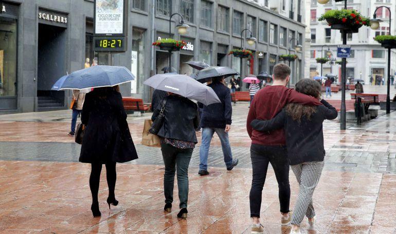 Lluvia en una calle comercial del centro de Oviedo.
