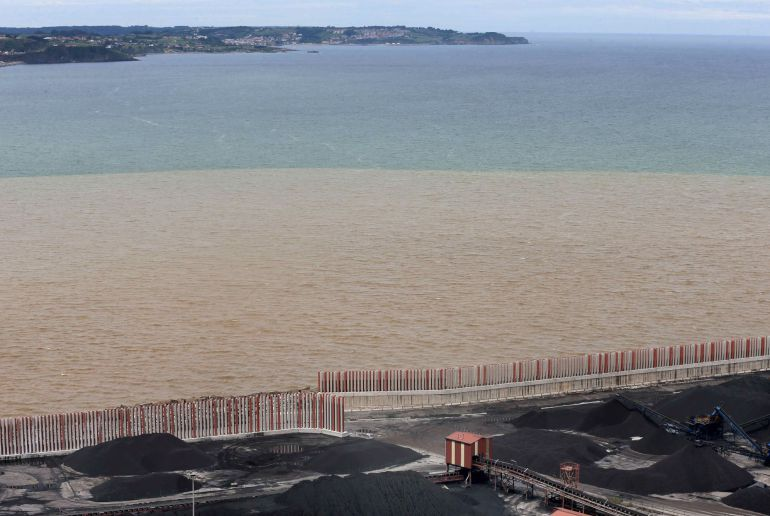 Aspecto que presenta el agua del Cantábrico en la desembocadura del río Aboño tras las fuertes lluvias caídas en las últimas horas en Gijón.