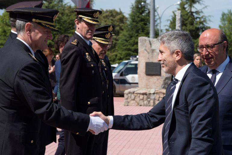 El ministro del Interior, Fernando Grande-Marlaska, acompañado por el director general de la Policía, Germán López, saluda al director de la Escuela Nacional de Policía de Ávila, José Luis Tejedor, en el acto de jura del cargo de la nueva promoción.