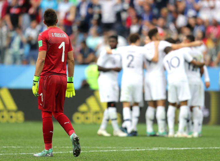Muslera mira la celebración de los jugadores franceses tras el gol de Griezmann.