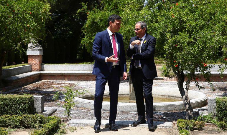 El presidente del Gobierno, Pedro Sánchez y el de la Generalitat, Quim Torra, durante un paseo por los jardines de la Moncloa