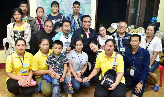 El primer ministro tailandés, Prayut Chan-o-cha, posa junto a familiares de los jugadores de fútbol atrapados en una cueva de Tham Luang.