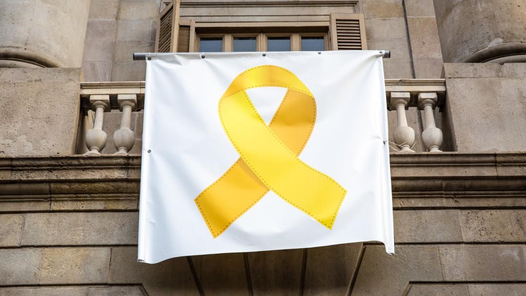 Un grupo de encapuchados descuelga el lazo amarillo del ayuntamiento de Barcelona