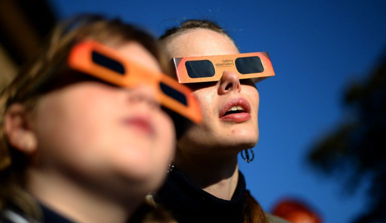 (FILES) This file picture dated May 10, 2013 shows people watching a partial solar eclipse at the Sydney Observatory. Die-hard eclipse junkies from around the world are expected to brave polar bears and frostbite in the Arctic on March 20, 2015 to savour three minutes of total darkness when the moon totally blocks the sun. The Norwegian archipelago of Svalbard, located 1,300 kilometres (800 miles) from the North Pole, is along with the Faroe Islands the only place the total eclipse will be visible. Elsewhere only a partial eclipse will be seen at best. AFP PHOTO / Saeed KHAN