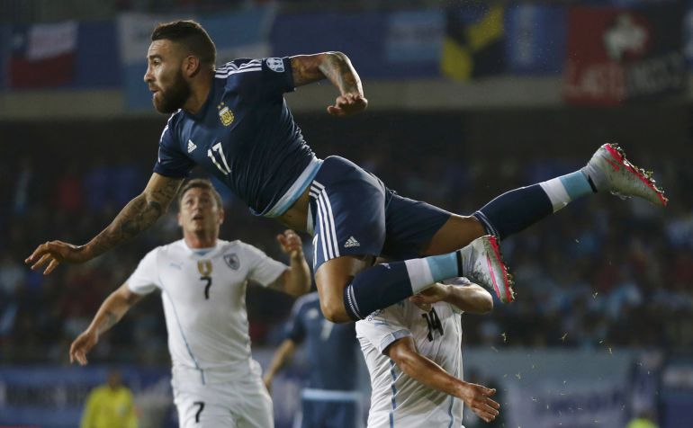 Argentina's Nicolas Otamendi jumps over Uruguay's Marcelo Lodeiro as Uruguay's Cristian Rodriguez (7) looks on during their first round Copa America 2015 soccer match at Estadio La Portada in La Serena, Chile, June 16, 2015. 