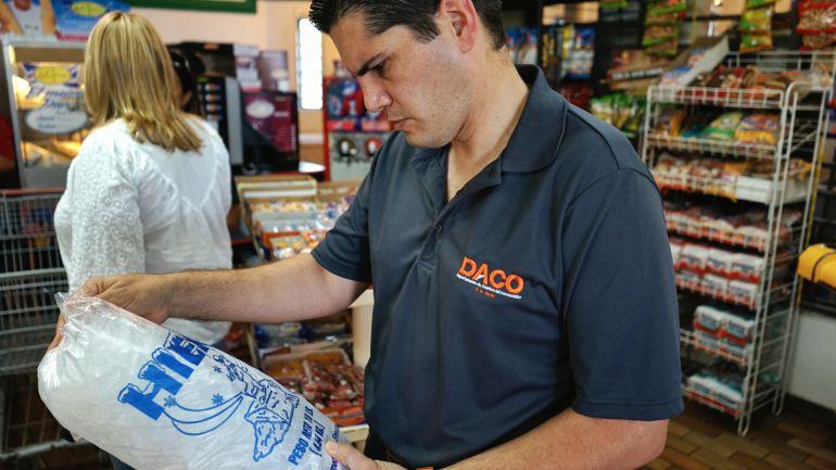 Un cliente adquiriendo una bolsa de hielo en un supermercado