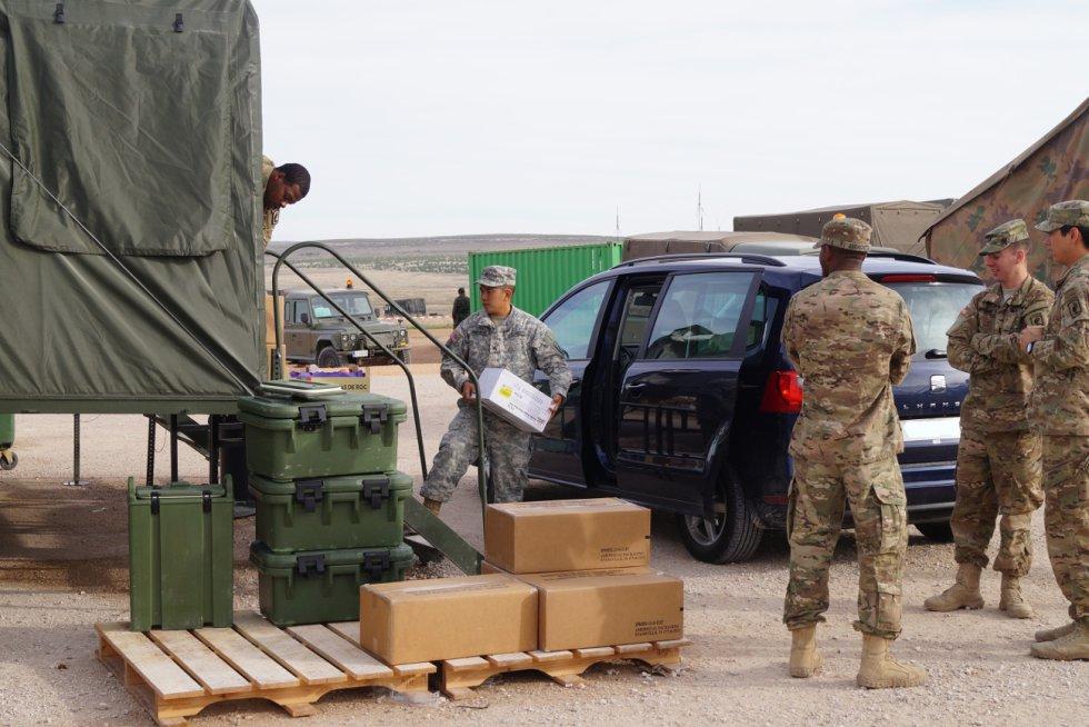 Un militar descarga una caja con comida en la cocina del campamento