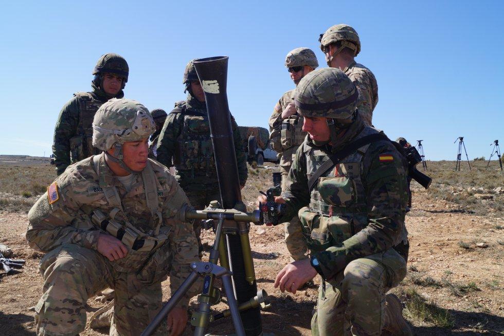 Un militar español explica cómo funciona el mortero a un militar estadounidense