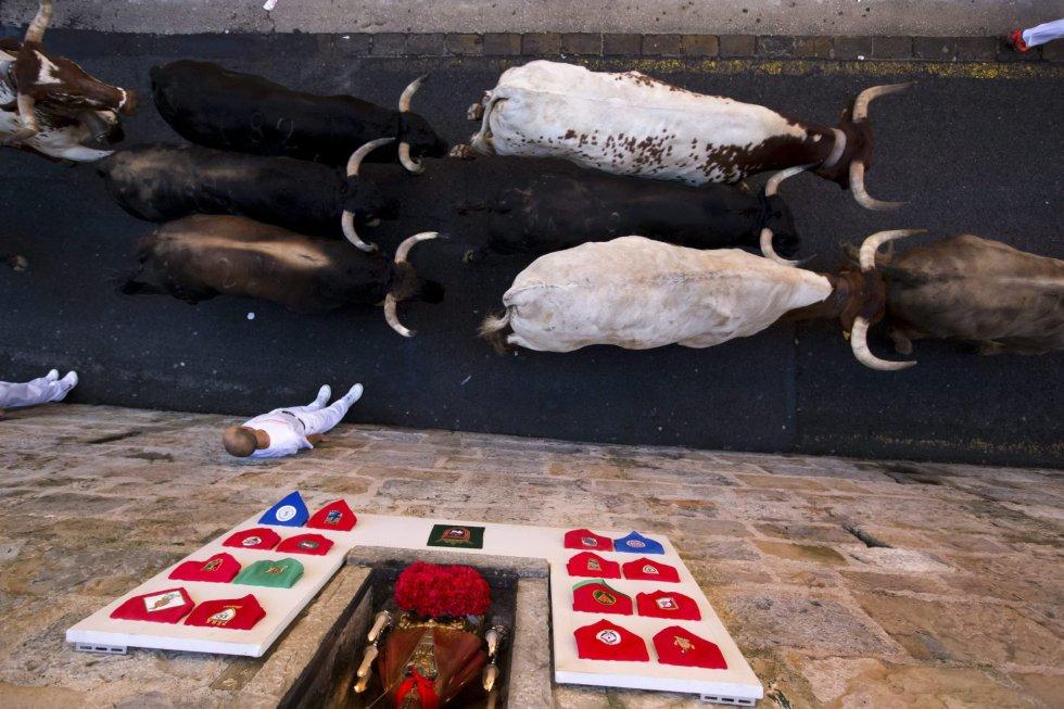 Corredores se pegan al muro mientras los toros de la ganadería Fuente Ymbro avanzan por la Cuestra de Santo Domingo.