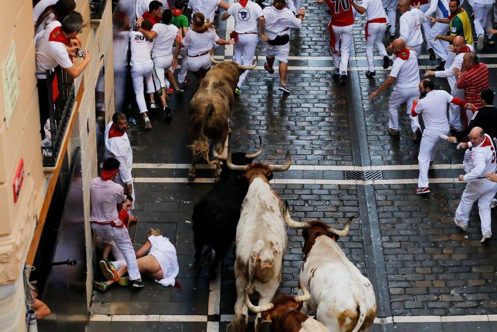 Una mujer cae al suelo ante los toros.