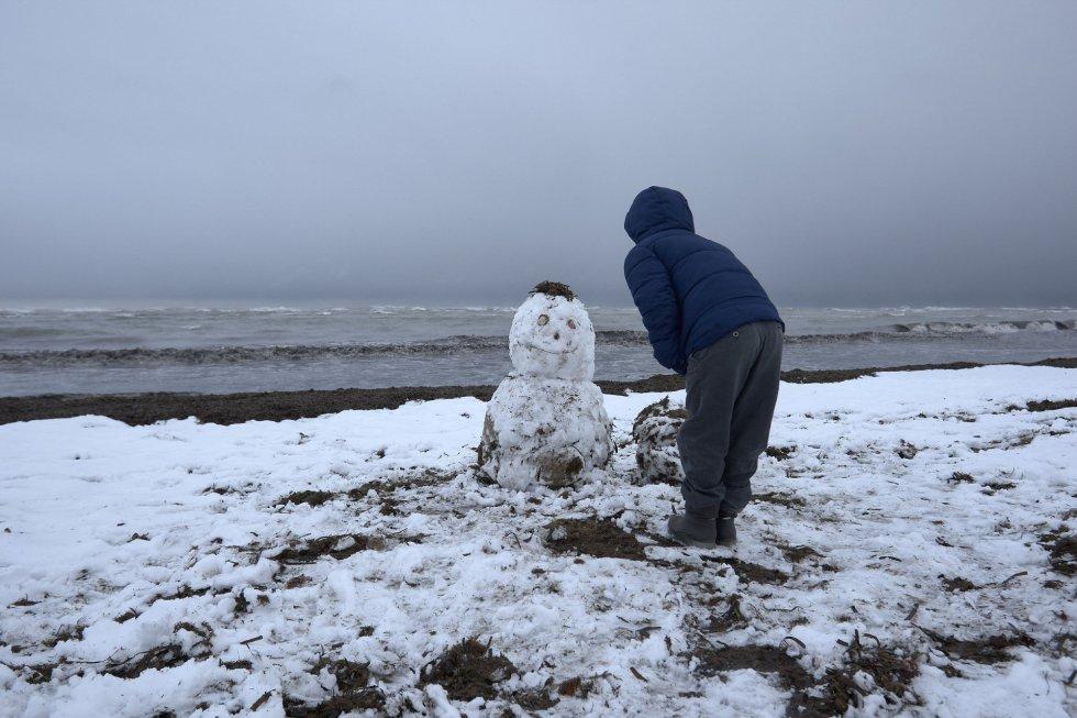 Un niño juega con un muñeco de nieve en la playa de Les Marines, en Denia.
