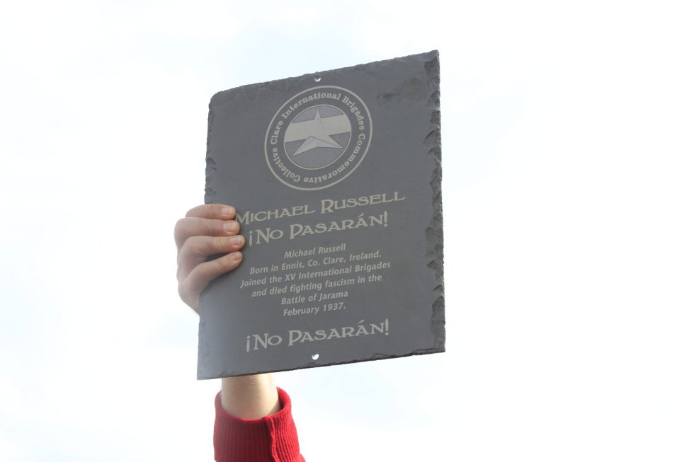 Un integrante de la marcha enseña a placa en reconocimiento a Michael Russell, un soldado caído a los dos días de comenzar la Batalla del Jarama, cuya familia se desconoce