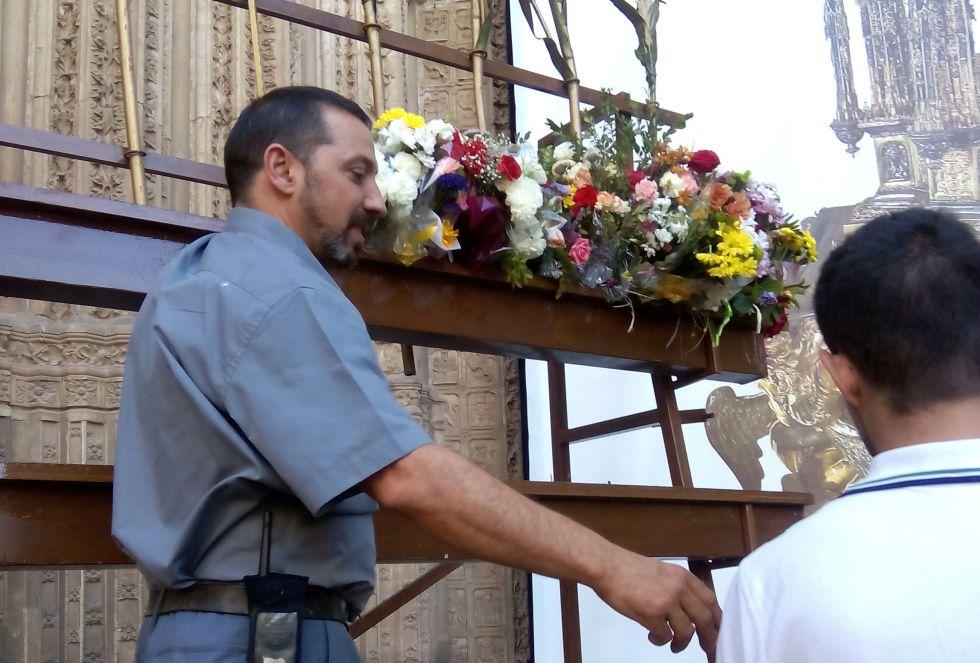 Un operario de la Catedral recoge los ramos de los niños