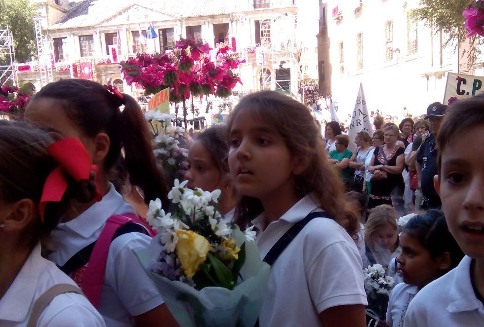 Los niños de varios colegios esperan su turno para entregar los ramos