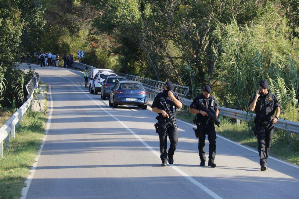 Tres agentes de los Mossos d'Esquadra caminan por la carretera de Subirats.