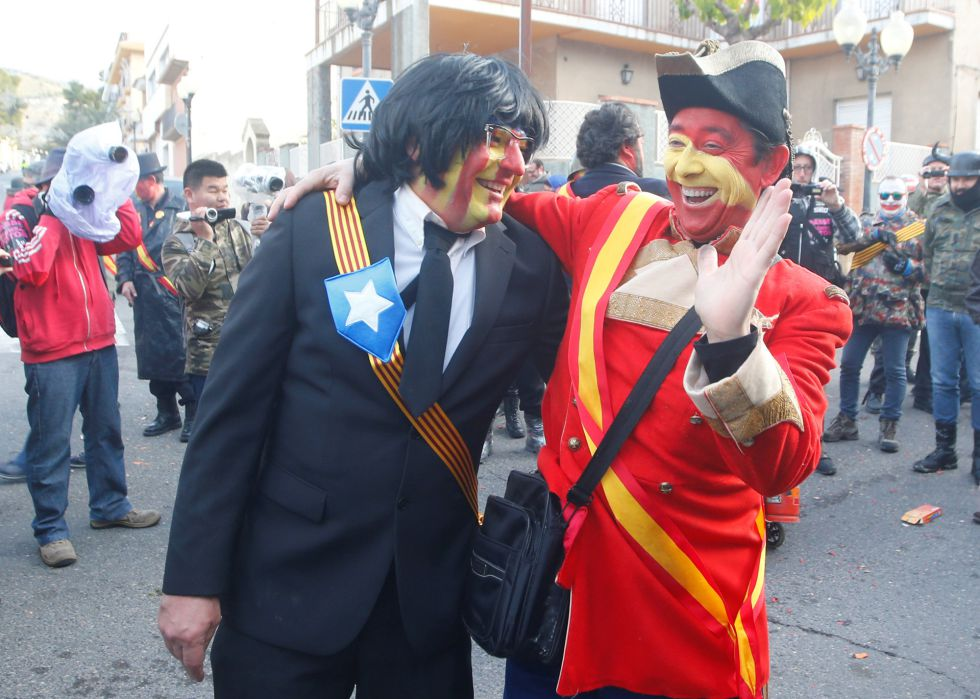 A reveller masked as former Catalonian President Carles Puigdemont (L) embraces with a fellow reveller in Spanish colours during the traditional Els Enfarinats (The Floured) festival in Ibi, Alicante Province, Spain December 28, 2016. REUTERS/Heino Kalis