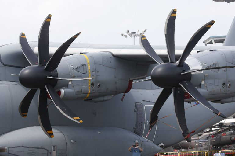 A man (bottom-C) is dwarft while taking photographs underneath the wing and propeller engines of Royal Malaysian Air Force (RMAF) Airbus A400 transport plane at the static display ahead of the Singapore Airshow at the Changi Exhibition Centre in Singapore, 04 February 2018. The Singapore Airshow will take place from 06 to 11 February 2018 and will showcase aviation and defense technologies from around the world. (Singapur, Malasia, Singapur)
