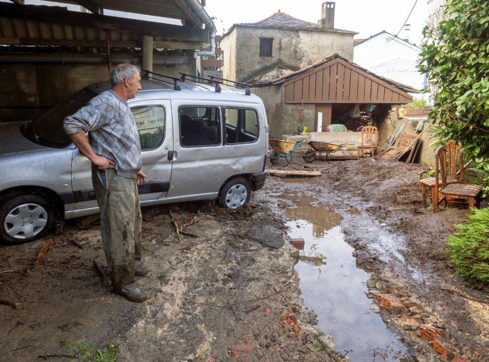 Una persona observa los daños en su casa, que fue alcanzada por la riada, llevándose a su paso un garaje y el asfalto de la calle.