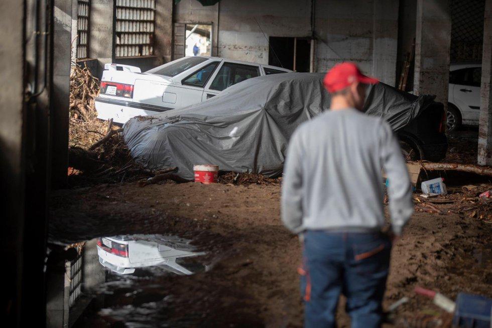 Una persona observa los daños en uno de los garajes afectados por la riada.