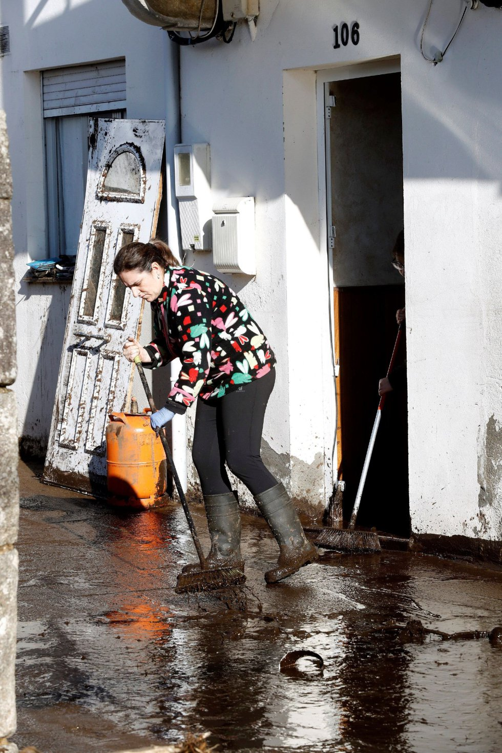 Una vecina limpia los restos de la riada junto a su vivienda en el barrio de Xunqueira.