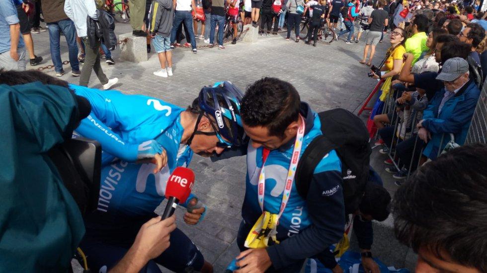 Oficiales de los equipos atienden a los ciclistas recién llegados