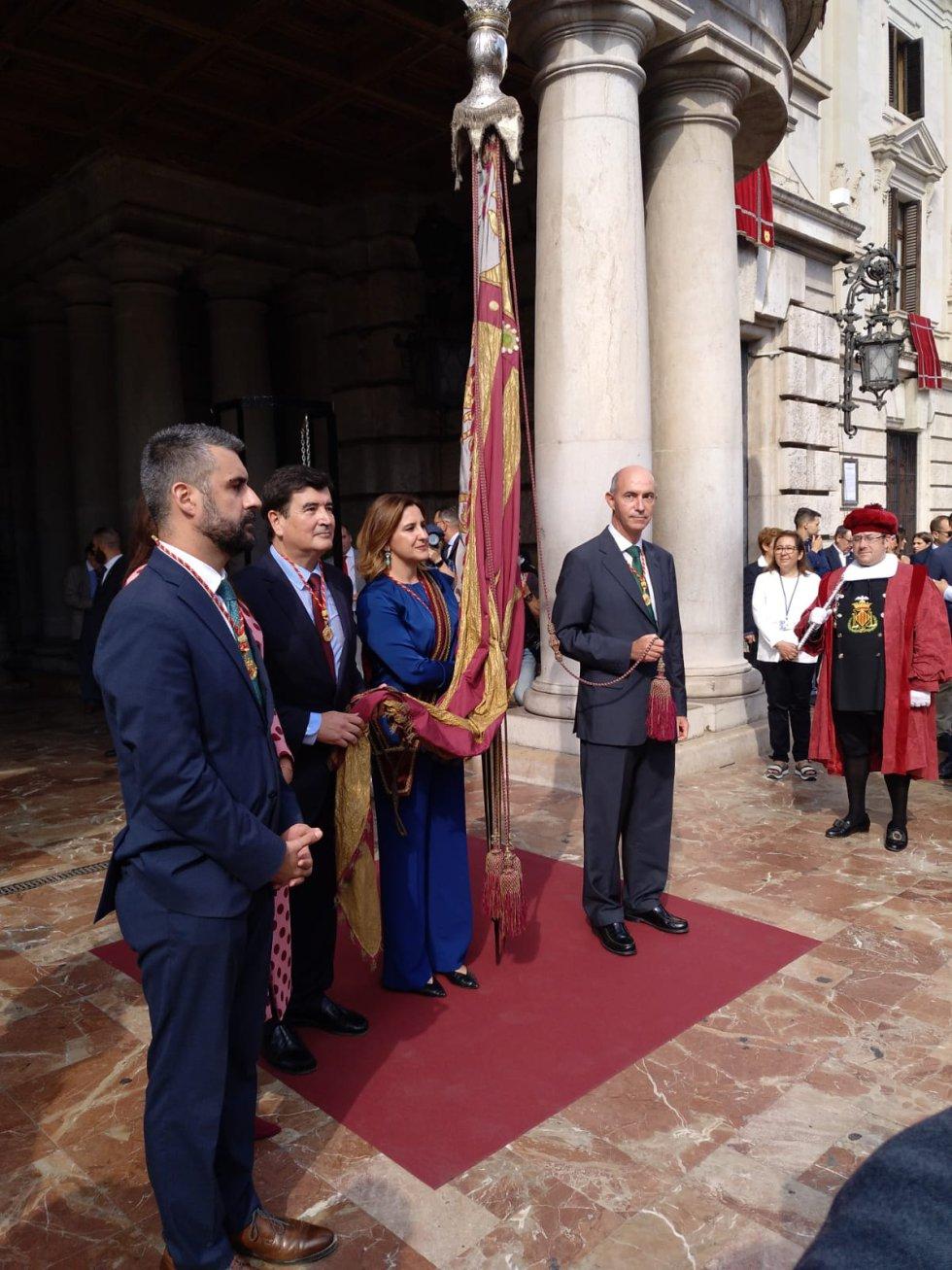 María José Catalá ha portado la bandera este año y ha contado con la ayuda del representantes del resto de fuerzas políticas del Ayuntamiento