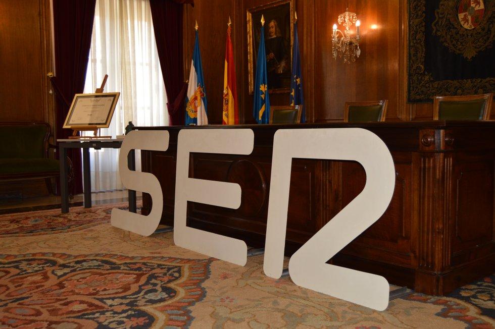 La mesa de las autoridades preparada con la imagen de la SER al frente