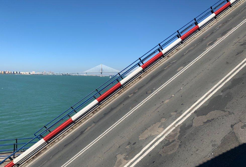 Uno de los semitramos móviles se eleva sobre la bahía de Cádiz, con el segundo puente al fondo