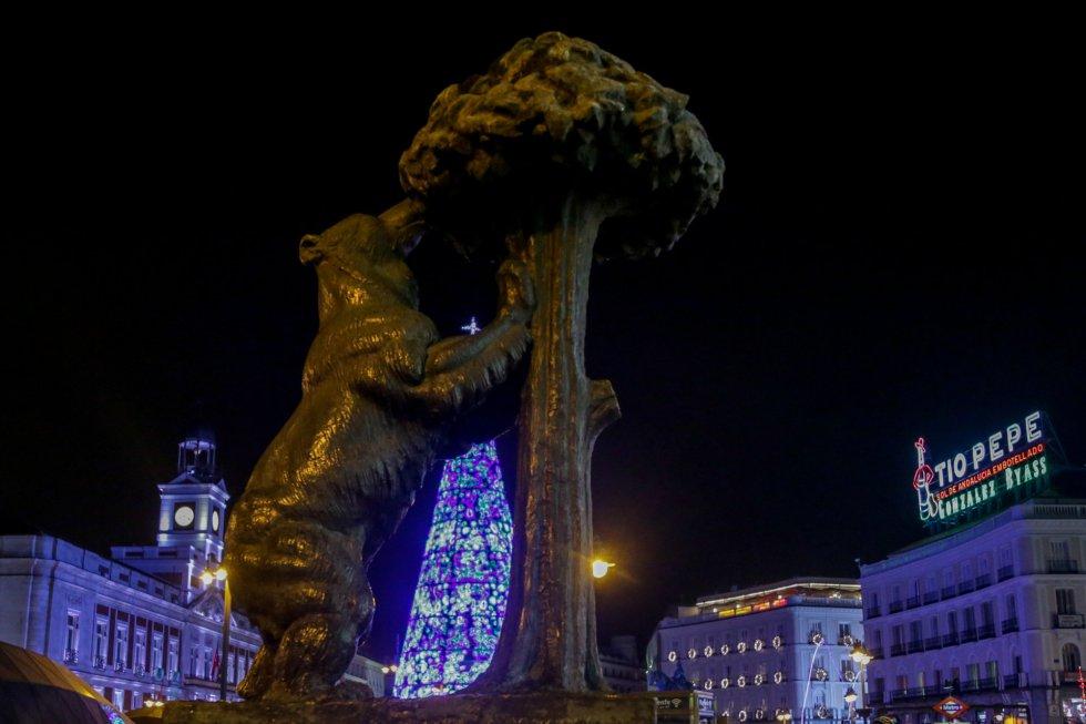 La escultura del 'Oso y el madroño' de la Puerta del Sol, y el árbol de Navidad de la plaza que hoy se ha encendido, en Madrid a 22 de noviembre de 2019