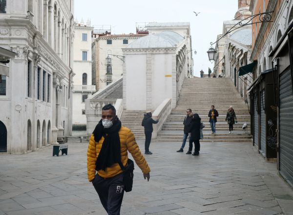 A man wearing a protective face mask walks through a street after the Italian government imposed a virtual lockdown on the north of Italy including Venice to try to contain a coronavirus outbreak, in Venice, Italy, March 9, 2020. REUTERS/Manuel Silvestri