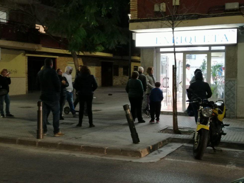 Vecinos de Gandia hacen cola en la calle para comprar en un comercio de la ciudad unas horas después de anunciarse el decreto del Estado de Alarma para toda España