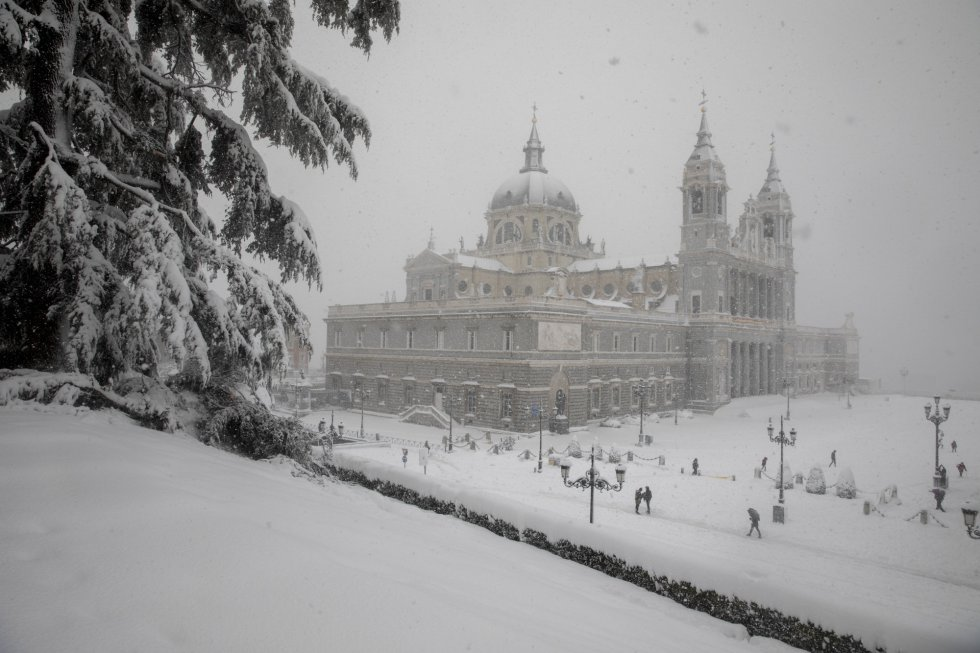 MADRID, SPAIN - JANUARY 09: People walk on the snow next to La Almudena Cathedral during heavy snowfall on January 09, 2021 in Madrid, Spain. Spain is on red alert for a second day due to storm Filomena, which has brought unusually cold weather and heavy snowfalls. The storm has caused cancelled services and transport disruption. (Photo by Pablo Blazquez Dominguez/Getty Images)