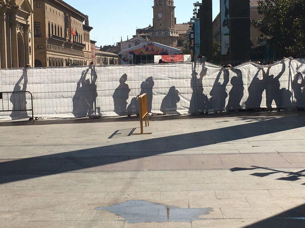 Sombras de los ciudadanos que buscan sortear la malla que rodea la plaza del Pilar para conseguir una imagen de la Virgen del Pilar.