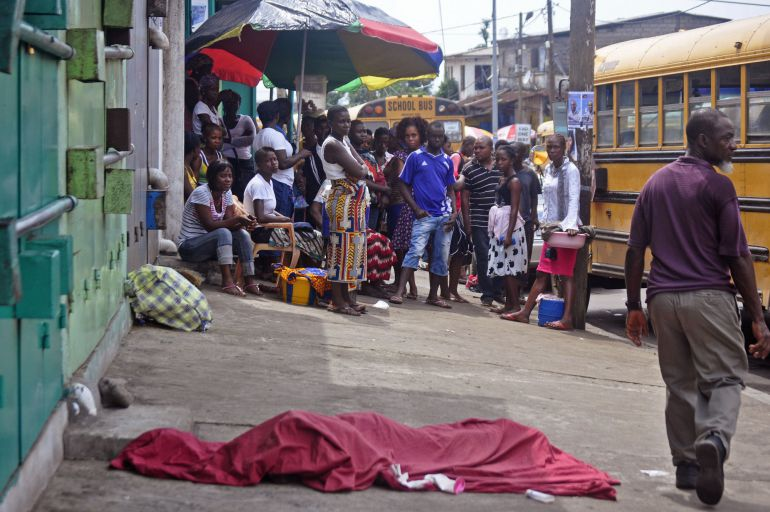 In this photo taken on Saturday, Nov. 22, 2014, the covered body, foreground, of a man suspected of dying from the Ebola virus, lies in the street as a person, right, walks past in the city center of Monrovia, Liberia.  As infection rates fall in Liberia, the information minister urged people on Thursday, Nov. 27, 2014,  to not let up the fight against Ebola, reiterating the goal of eradicating the disease by the end of the year.  (AP Photo/ Abbas Dulleh)