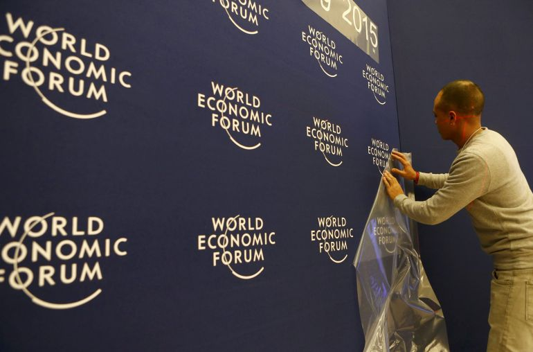 A worker sets up logos of the World Economic Forum (WEF) at the congress center in the Swiss mountain resort of Davos January 20, 2015. More than 1,500 business leaders and 40 heads of state or government will attend the January 21-24 meeting of the WEF to network and discuss big themes, from the price of oil to the future of the Internet. This year they are meeting in the midst of upheaval, with security forces on heightened alert after attacks in Paris, the European Central Bank considering a radical government bond-buying programme and the safe-haven Swiss franc rocketing.    REUTERS/Ruben Sprich (SWITZERLAND  - Tags: POLITICS BUSINESS)