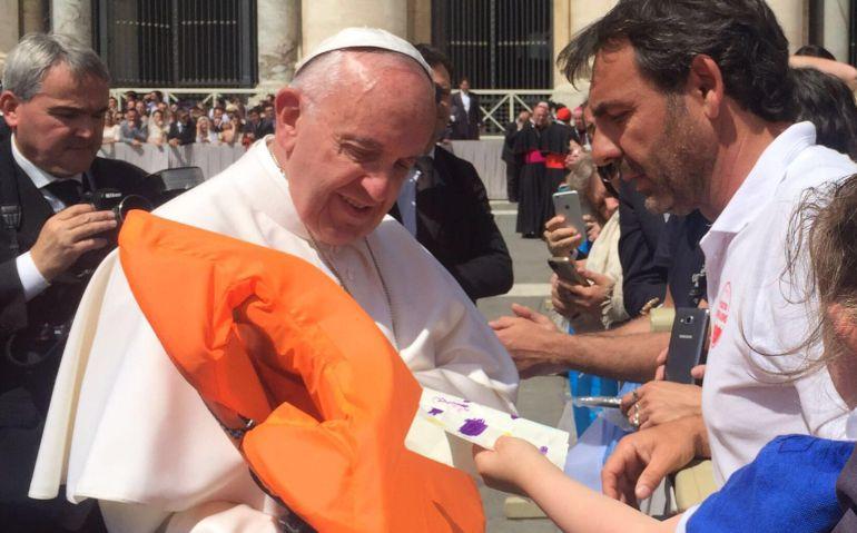 Óscar Camps, entregando un chaleco al papa