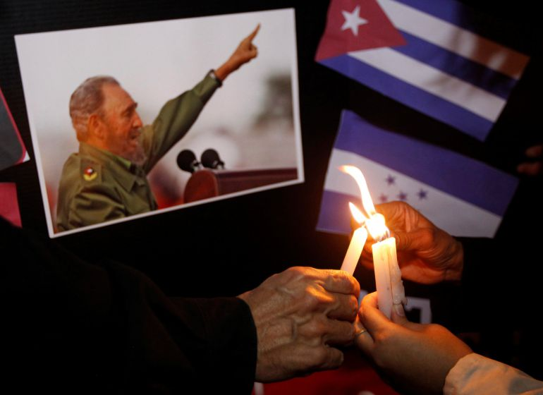 People place candles beside a picture of Fidel, as part of a tribute, following the announcement of the death of Cuban revolutionary leader Fidel Castro, in Tegucigalpa, Honduras November 26, 2016.