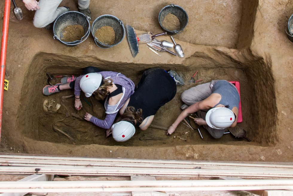 Antropólogos forenses, arqueólogos y voluntarios limpian los huesos de uno de los cadáveres hallados.