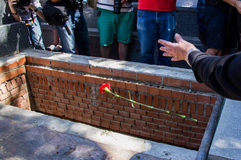 Los asistentes al sepelio de Timoteo Mendieta arrojan flores rojas sobre su féretro.