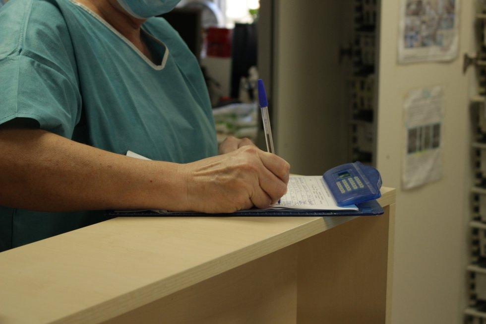 Una trabajadora apuntando en una hoja datos de un paciente de una de las plantas destinadas al covid