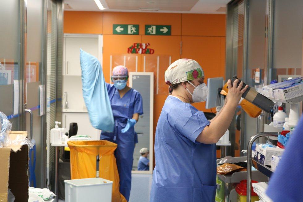 Dos trabajadores del Clinic de Barcelona colocando algunos utensilios en la UCI