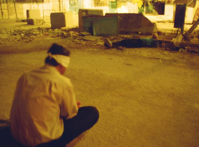 Dos palestinos con los ojos vendados y esposados esperan tirados en el suelo a que los soldados les dejen marcharse
