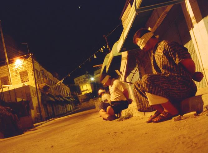En sus ratos muertos los soldados reflejan su día a día como ocupantes. En la imagen un grupo de civiles retenidos en plena calle y de noche