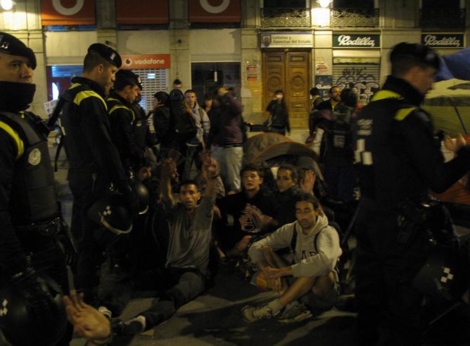 Jóvenes manifestantes en la Puerta del Sol de Madrid durante el desalojo de la concentración